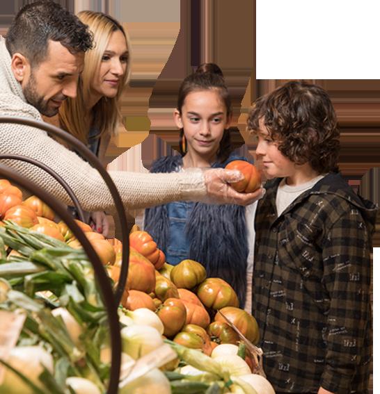 Familia en Eroski y niño oliendo tomate