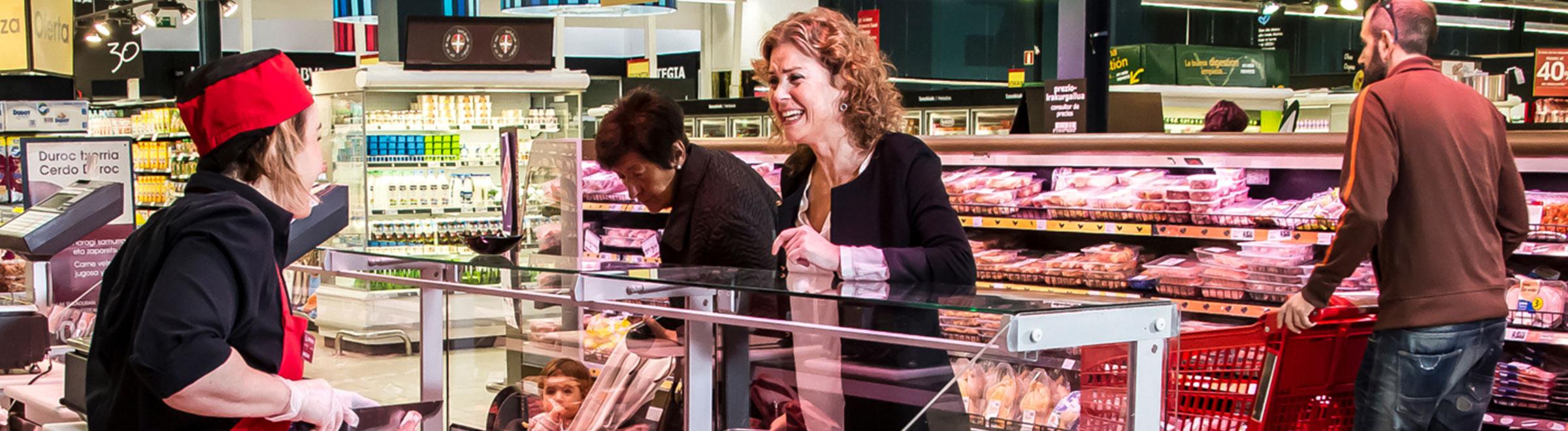 Mujer sonrie a empleada en supermercado Eroski