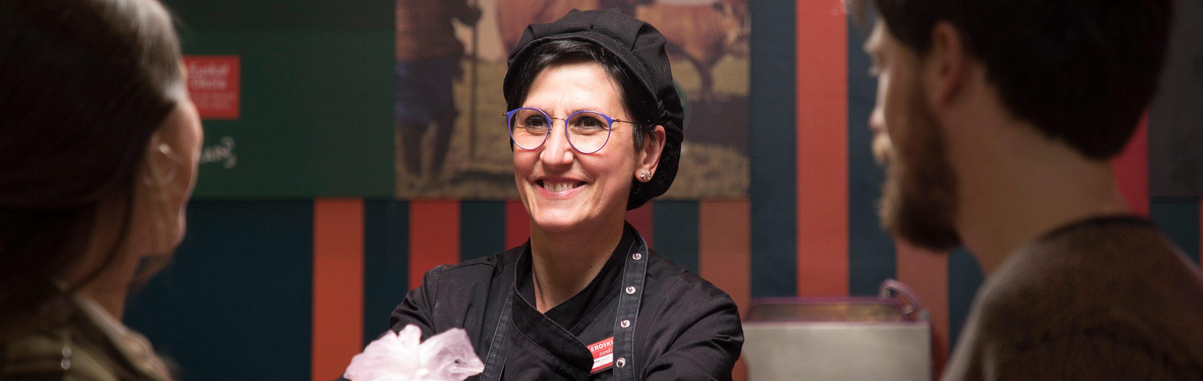 Trabajadora de Eroski sonrie a clientes