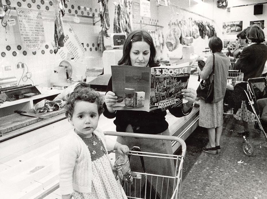 Mujer lee revista Eroski con niña en carro