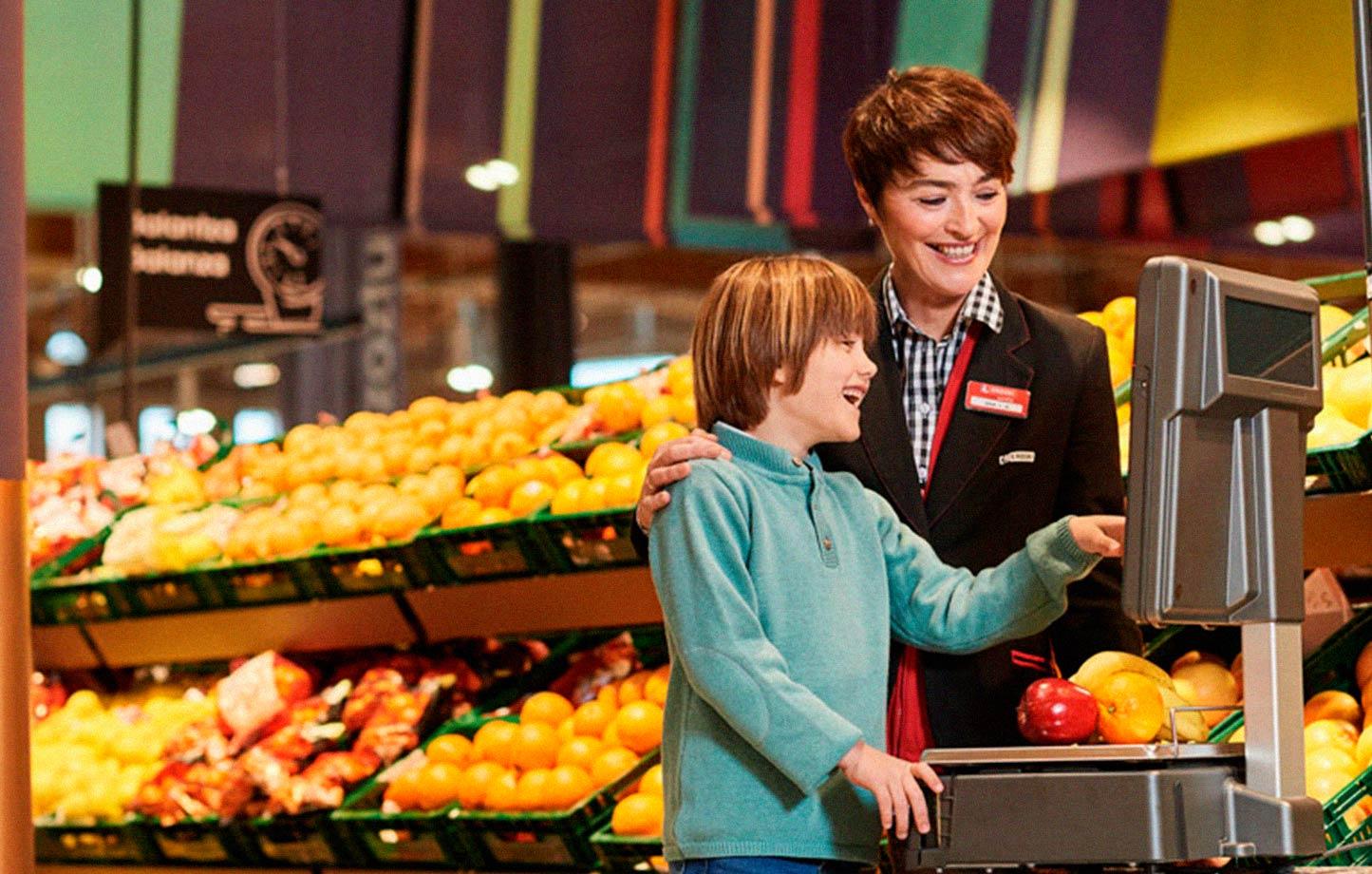 Empleada Eroski ayuda a niño a pesar la fruta